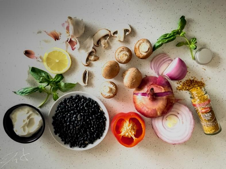 Para las burguers: · 2 tazas de frijoles negros (250 g) remojados 8-12 horas · 1/2 cebolla morada grande (150 g) · 8 champiñones Portobello (150 g) · medio pimiento rojo (100 g) · 3 dientes de ajo (15 g) · pan rayado integral · 3 cucharaditas de curry ( o pimienta y cúrcuma) · AOVE (aceite de oliva virgen extra) · sal marina Para la crema agria: · un yogur entero de cabra eco · 2 cucharaditas de zumo de limón · 1 cucharadita de vinagre de manzana · 8 hojas de albahaca · sal y pimienta negra.