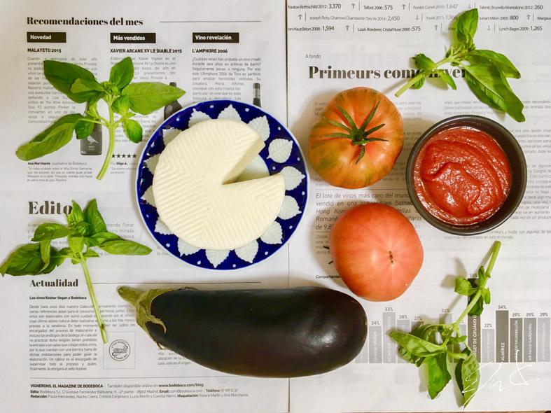 · 1 berenjena mediana (350g) · 2 tomates pequeños (350g) · 100 g queso tierno de cabra eco · 200 g tomate frito · 5 ramas de albahaca o un puñado de espinacas · 2-3 dientes de ajo picados · AOVE (aceite de oliva virgen extra) · pimienta negra · sal marina