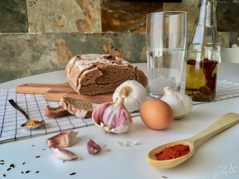 · 1 rebanada de pan integral de centeno duro · 1 diente de ajo · 1 huevo de gallina feliz, ósea Eco · 1 cucharadita de pimentón dulce de la Vera. · 1/2 cucharadita de cúrcuma (opcional) · una pizca de comino · 2-3 vasos de agua · 4 cucharadas de AOVE (aceite de oliva virgen extra) · sal