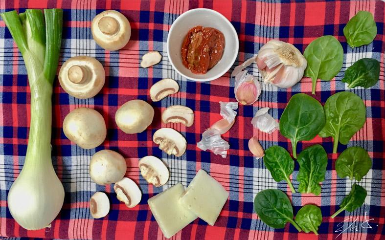 · 12 champiñones blancos o Portobello medianos( 250 g) · 1 trocito de cebolleta (40 g) puede ser la parte verde · 1 puñado de espinacas baby o perejil (25 g) · 2 tomates secos · 1 dado de queso de cabra eco (15 g) · 1 pizca de pimienta molida · 1 pizca de cúrcuma · 2 dientes de ajo · 4 cucharadas de AOVE (aceite de oliva virgen extra) · sal marina