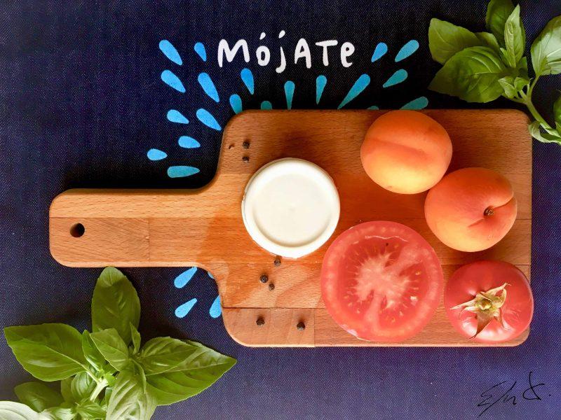 · 1 tomate de bola pequeño (80-100 g) · 1-2 albaricoques (100 g) · 6-7 hojas de albahaca, de rúcula o de espinacas · 1 mini-queso fresco eco de cabra (100 g) · AOVE · vinagre de Modena bajo en azúcar · pimienta negra · sal marina