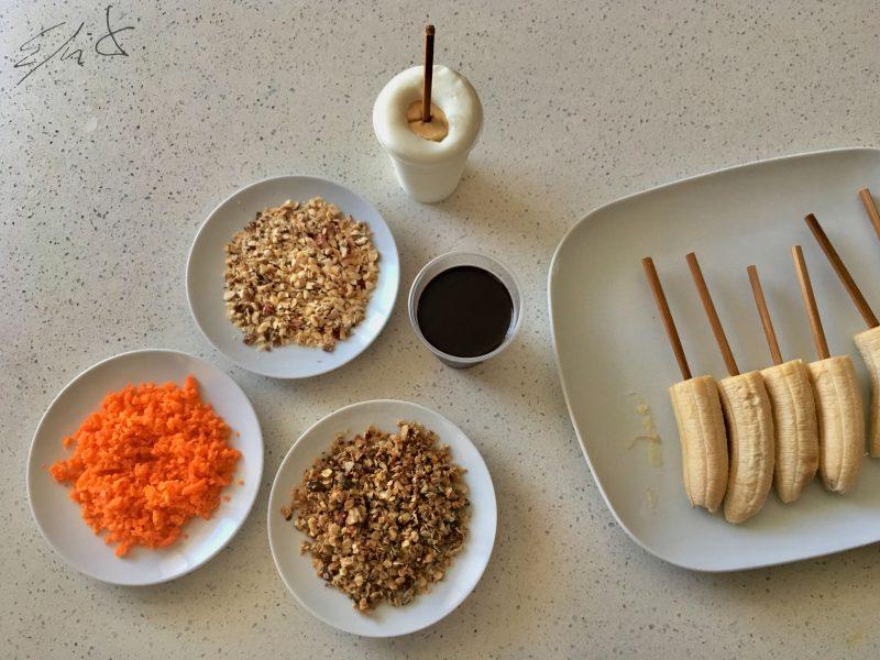· 4 plátanos de canarias. · 1 tableta de chocolate negro 80 % o más de cacao (100 g) · 1 vasito de yogur de oveja eco natural y sin azúcar (100 g) · 1 puñado de granola o muesli casero sin azúcar (30 g) · 1 zanahoria rallada · 1 puñado de avellanas tostadas picadas (25 g) · 2 pares de palillos de bambú para shusi cortados por la mitad.